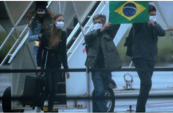 Pasajeros salen de uno de los aviones en los que fueron repatriados de la ciudad china de Wuhan 34 brasileños y sus parientes