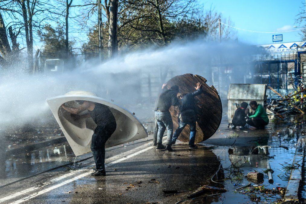 Los migrantes se refugian detrás de un contenedor de basura