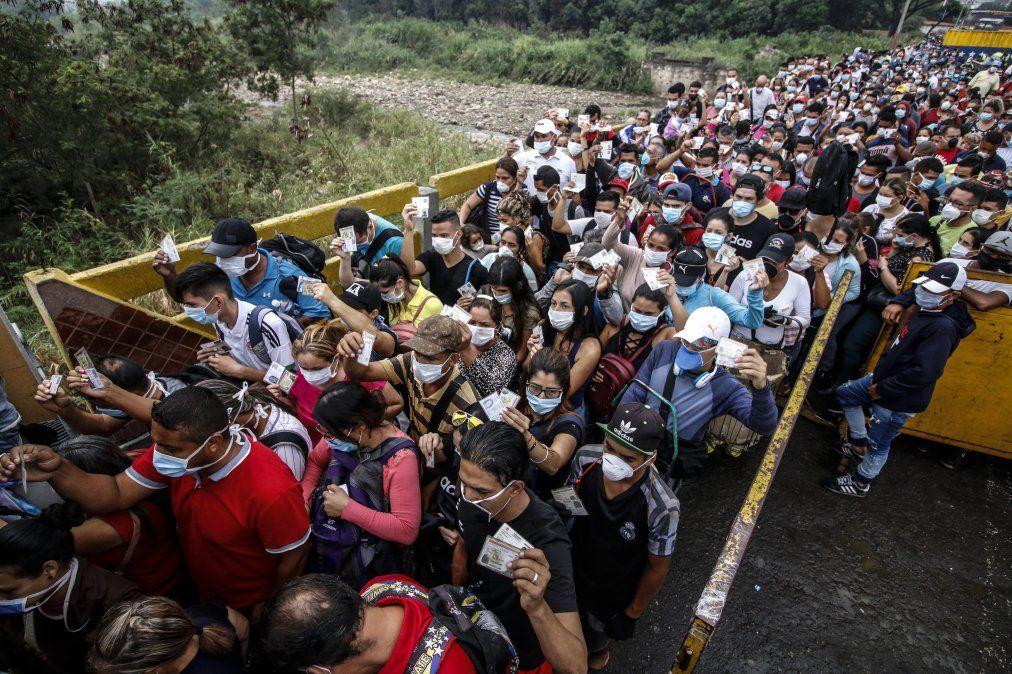 Personas que van de Venezuela a Colombia con mascarillas protectoras como medida de precaución para evitar contraer el nuevo coronavirus