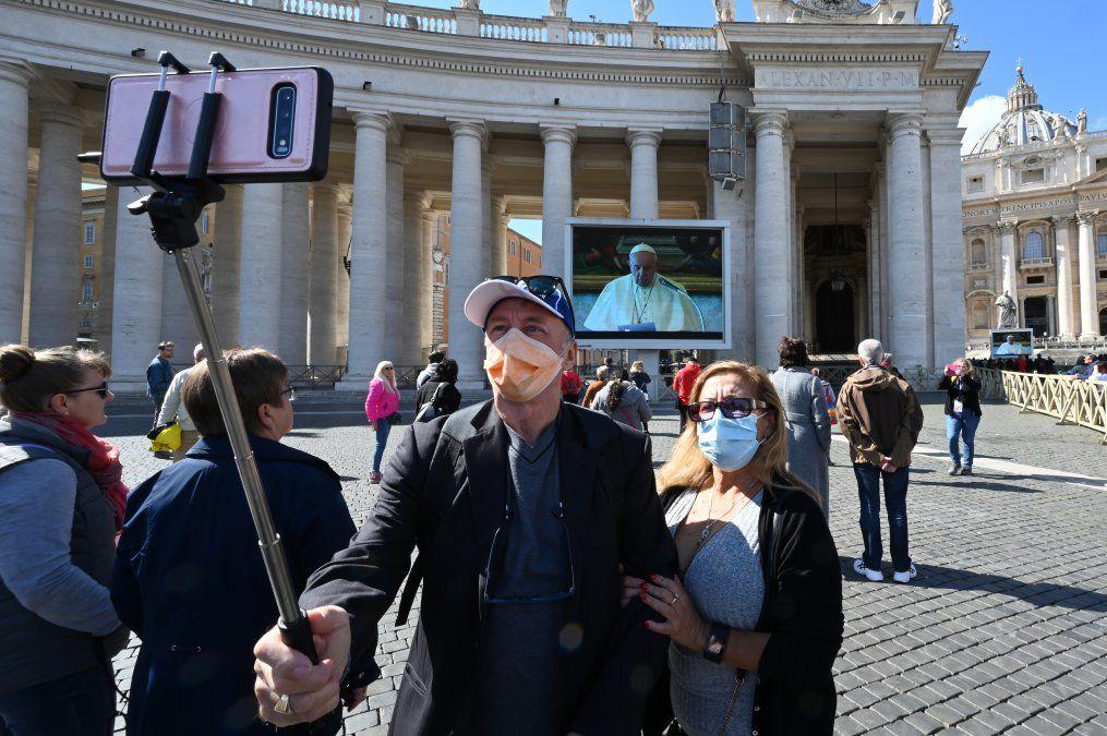 Una pareja toma una selfie frente a una pantalla con una audiencia en vivo del papa Francisco en el Vaticano