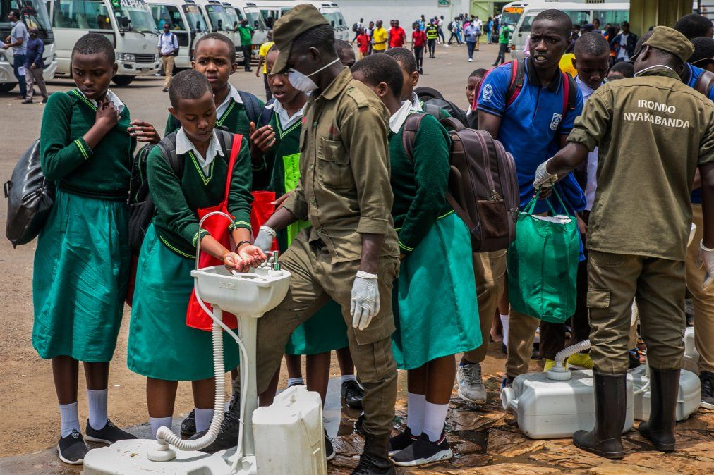 Los estudiantes de secundaria se lavan las manos en un punto temporal de lavado de manos antes de regresar a casa
