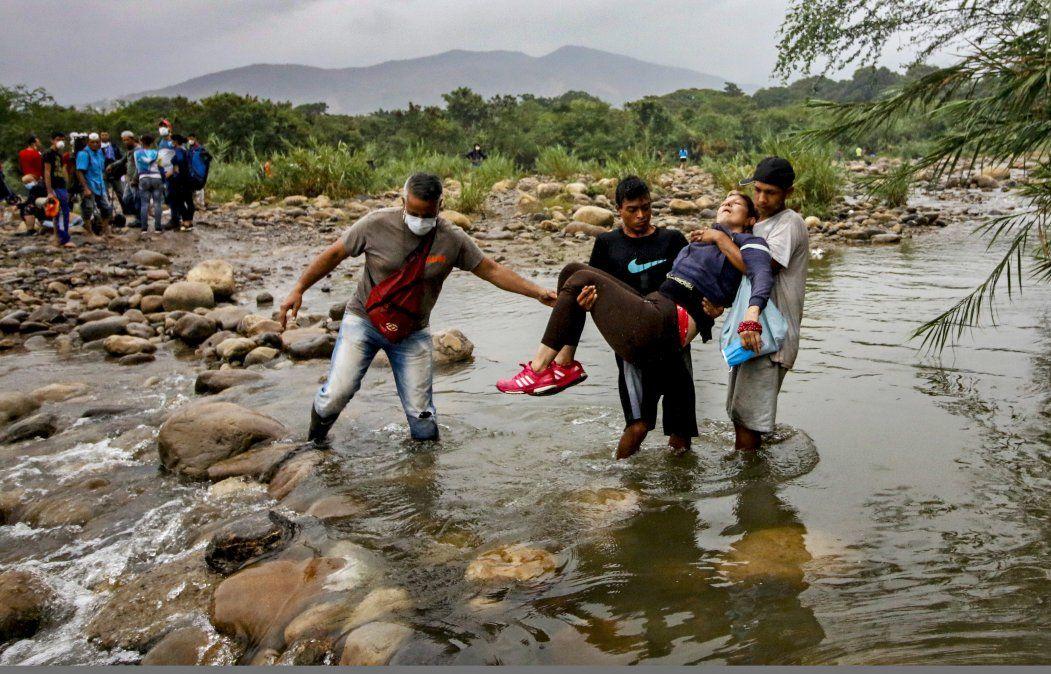 Ciudadanos venezolanos con mascarillas protectoras para prevenir la propagación del coronavirus llevan a una mujer inconsciente mientras intentan ingresar a Colombia