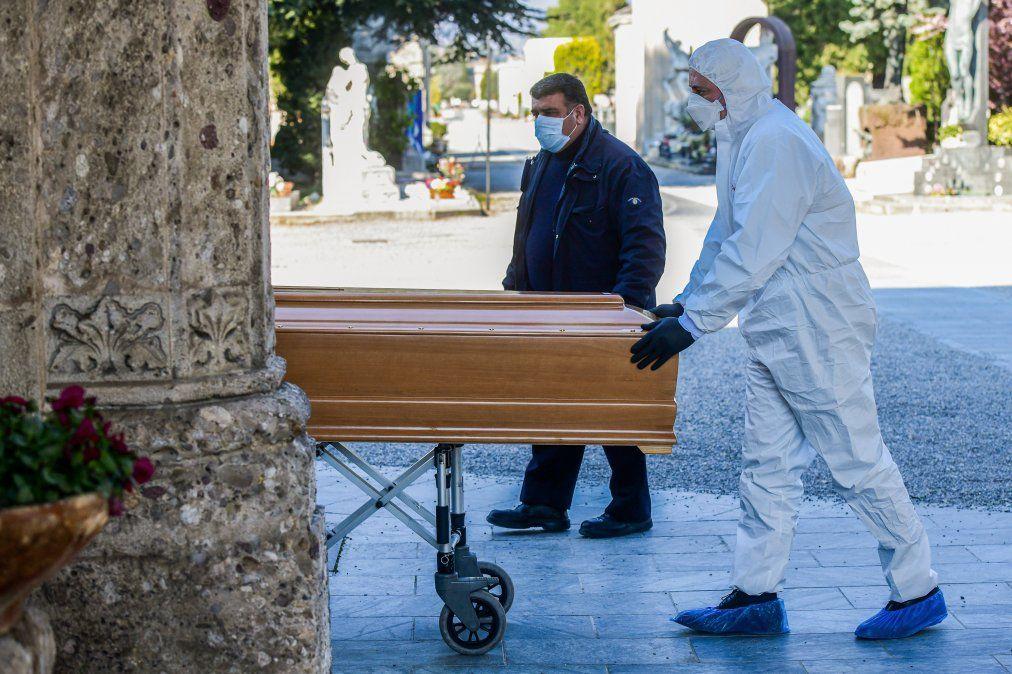 Trabajadores de una funeraria con máscara facial y un ataúd ingresan al cementerio de Bérgamo