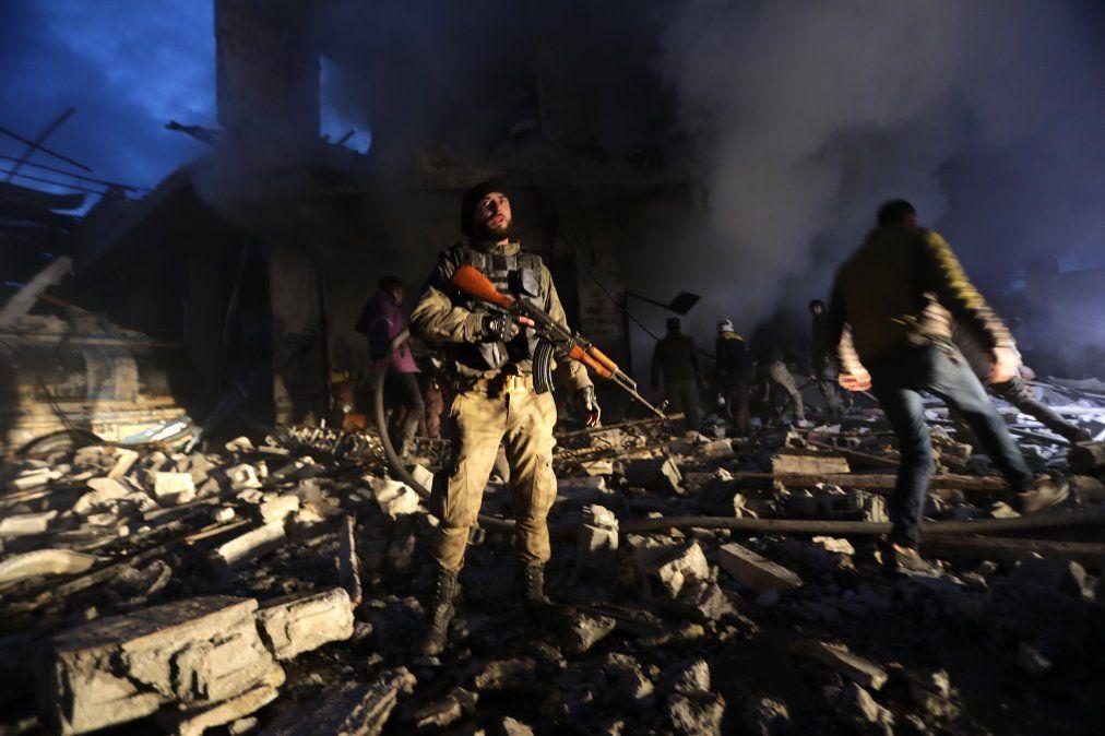 Los miembros de la defensa civil siria (Cascos blancos) y las fuerzas sirias respaldadas por Turquía buscan víctimas tras la explosión de un coche bomba