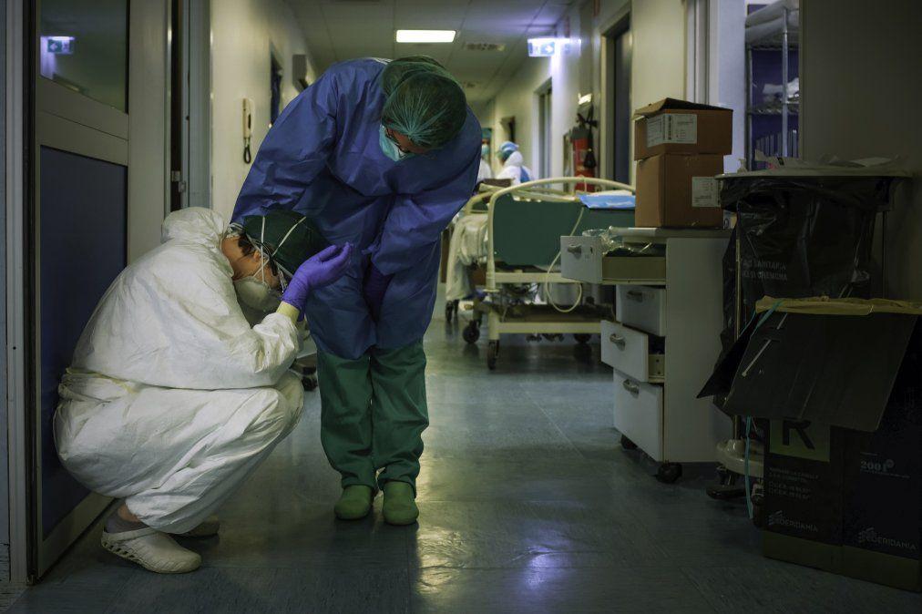 Una enfermera con máscara protectora y equipo consuela a otra mientras cambian de turno el 13 de marzo de 2020 en el hospital Cremona