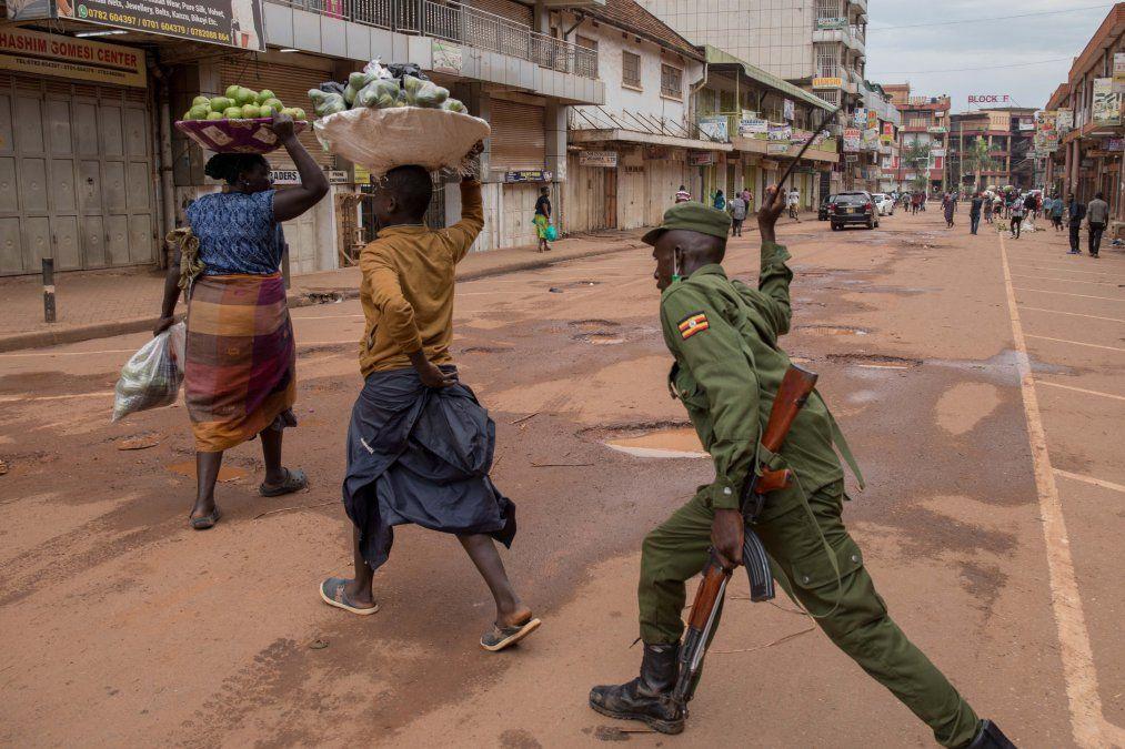 Un oficial de policía golpea a una vendedora de naranjas en una calle de Kampala