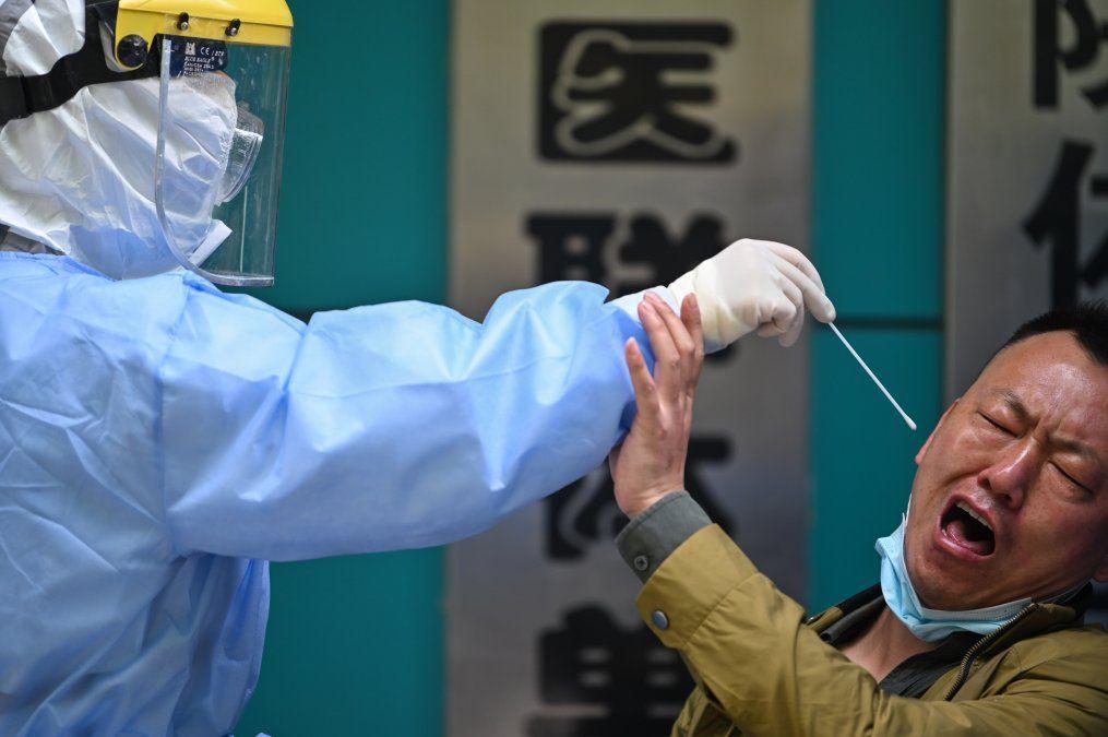 Un hombre que se está haciendo la prueba del nuevo coronavirus COVID-19 reacciona cuando un trabajador médico toma una muestra
