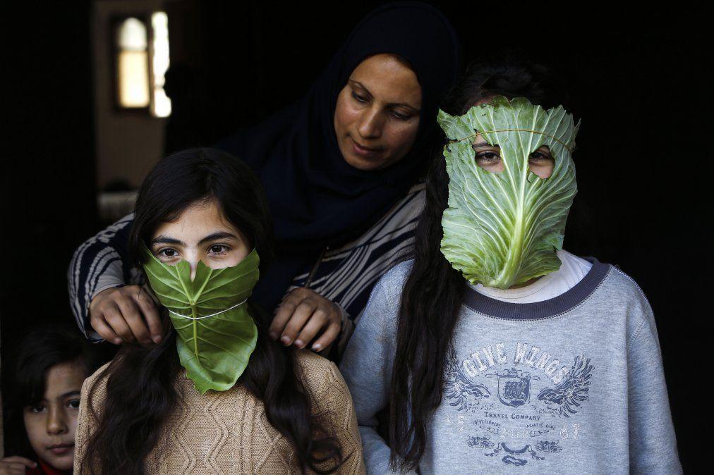 Una madre palestina entretiene a sus hijos con máscaras improvisadas hechas de repollo mientras cocina en Gaza
