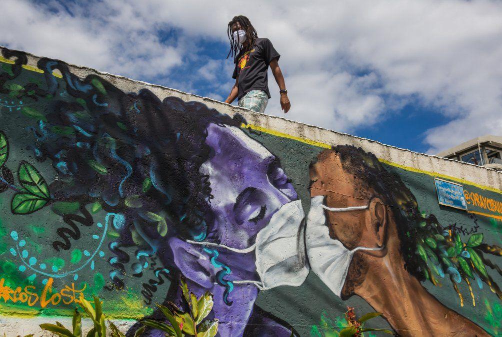 Un hombre con una máscara facial pasa junto a un graffiti del artista Marcos Costa en la entrada de la favela Solar de Unhao en Salvador