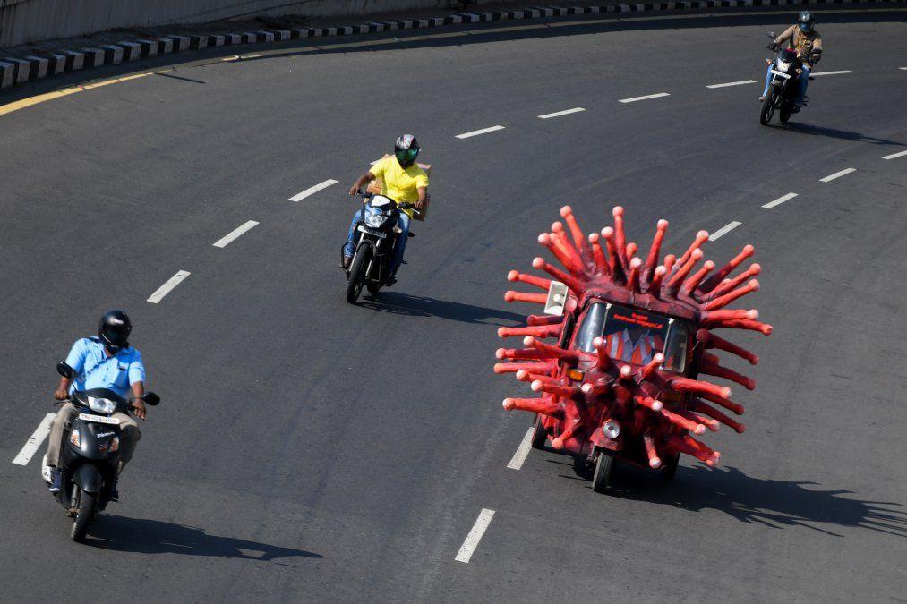 Un trabajador de salud municipal conduce un auto-rickshaw decorado como un modelo de coronavirus en India