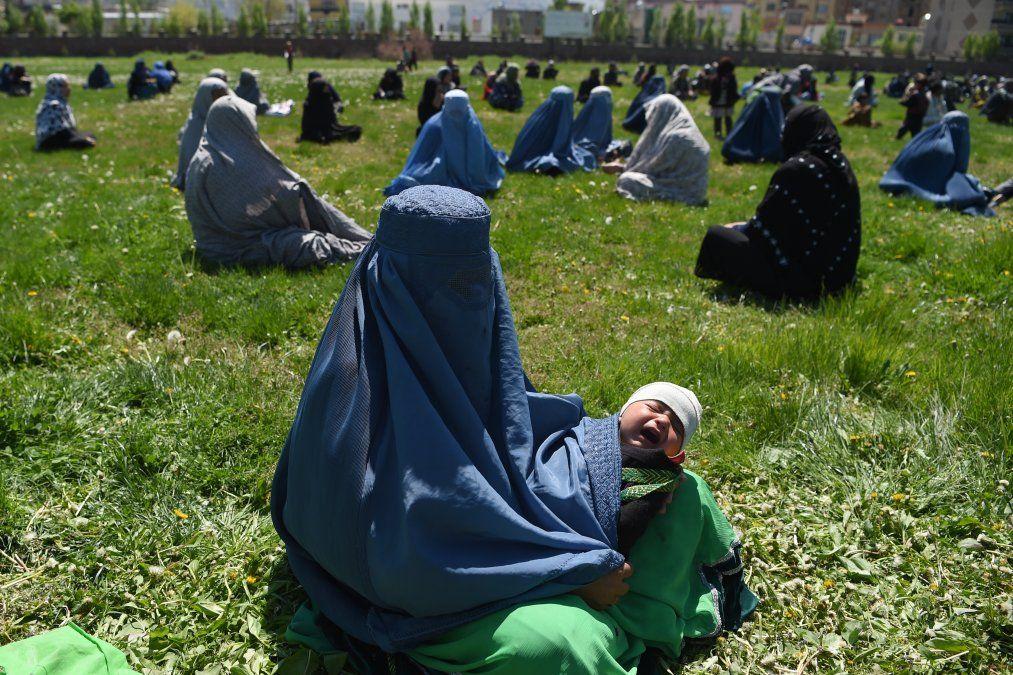 Una mujer que lleva un burka sostiene a su hijo mientras espera recibir trigo gratis del comité de emergencia en Kabul
