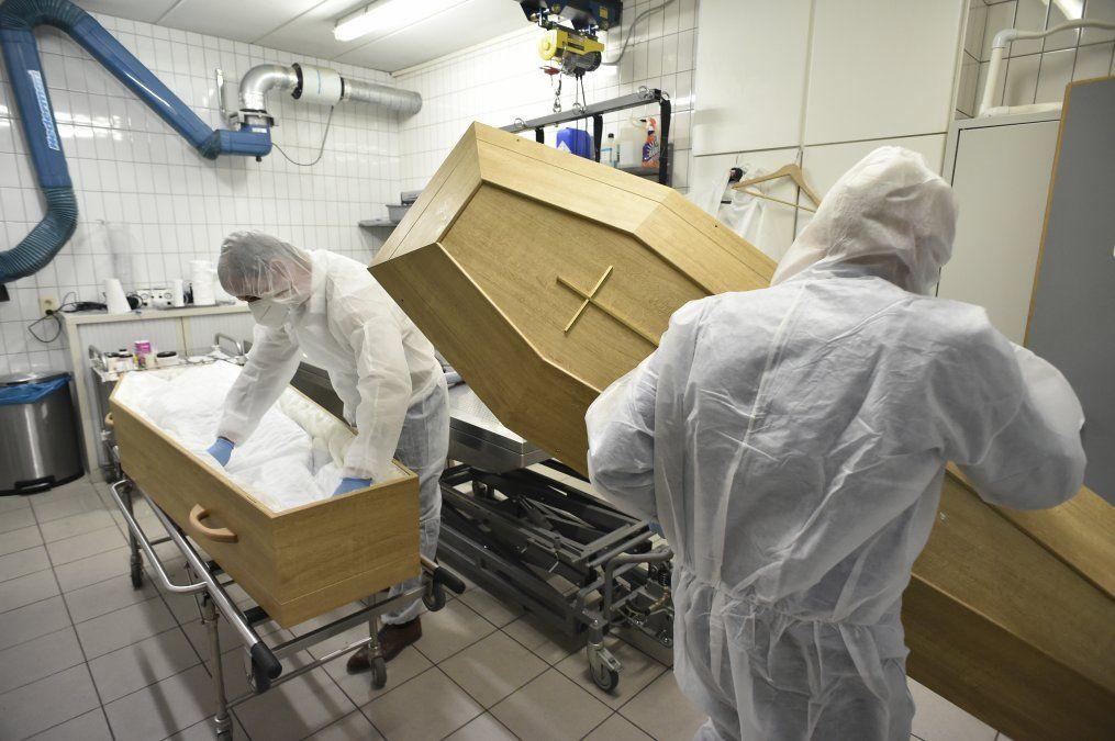 Los empleados de la funeraria Chaudoir cierran el ataúd con el cuerpo de una persona que murió del COVID-19 en una morgue en Namur