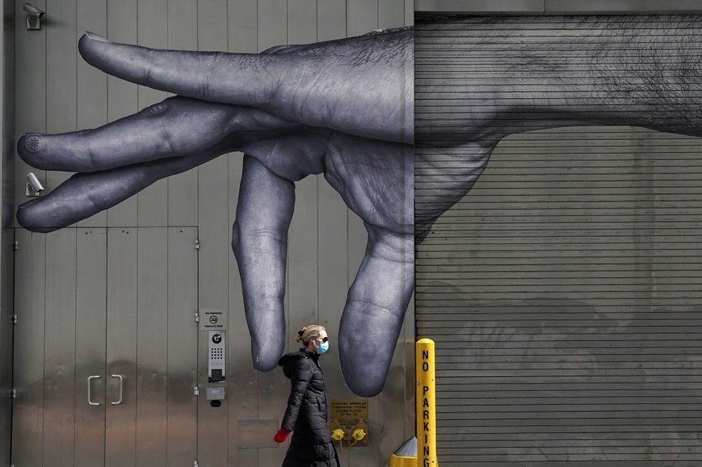 Una mujer con tapabocas pasa frente a un mural de una mano sobre un edificio en Nueva York