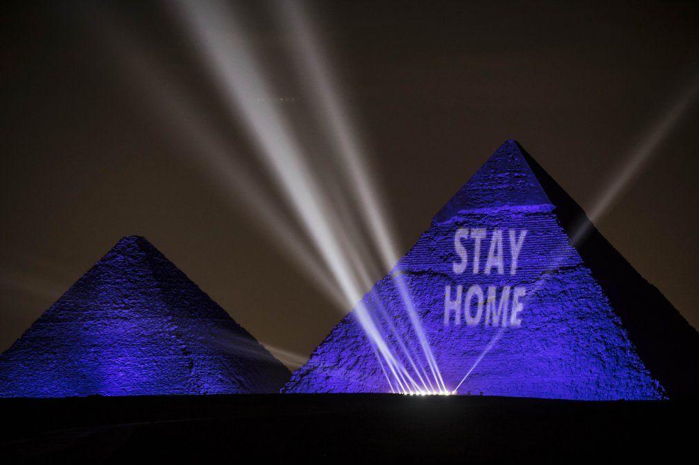 Grandes Pirámides iluminadas con luz azul y el mensaje Quédese en casa en la meseta de Giza
