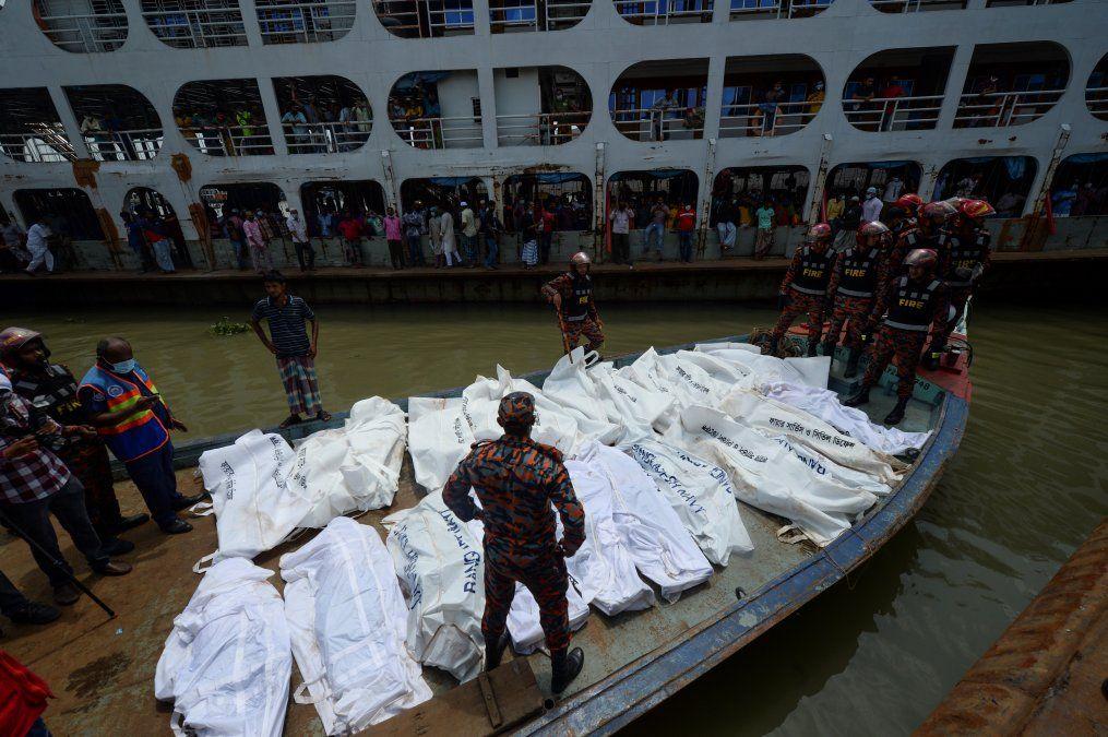 Los equipos de rescate traen cuerpos de víctimas después de que un ferry volcara en la terminal de ferry de Sadarghat