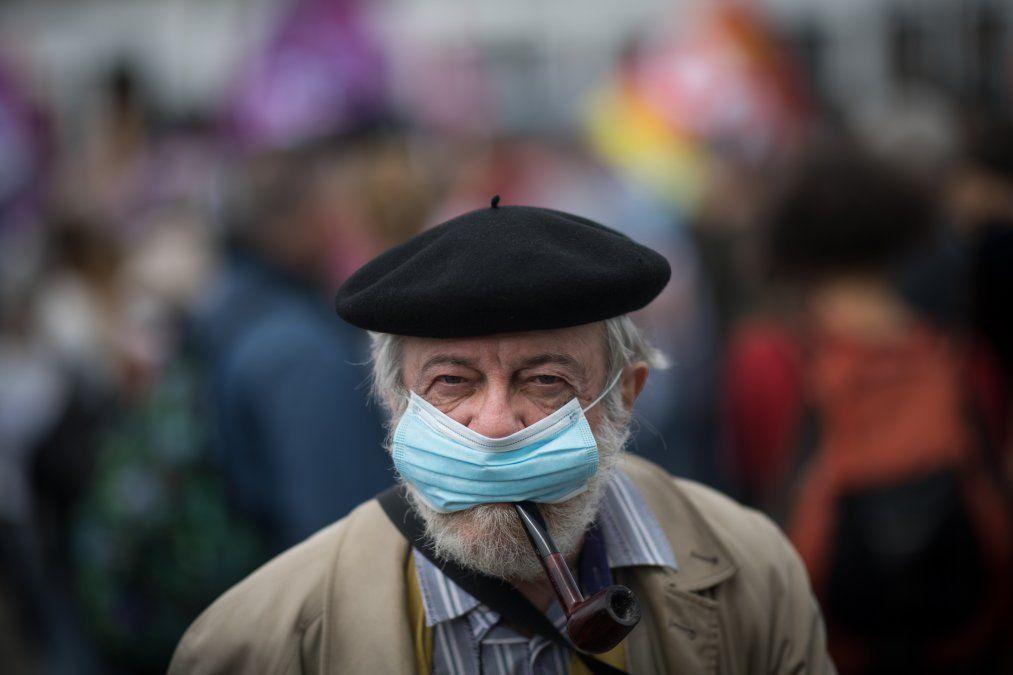 Un hombre fuma pipamientras usa una máscara facial durante una manifestación enNantes