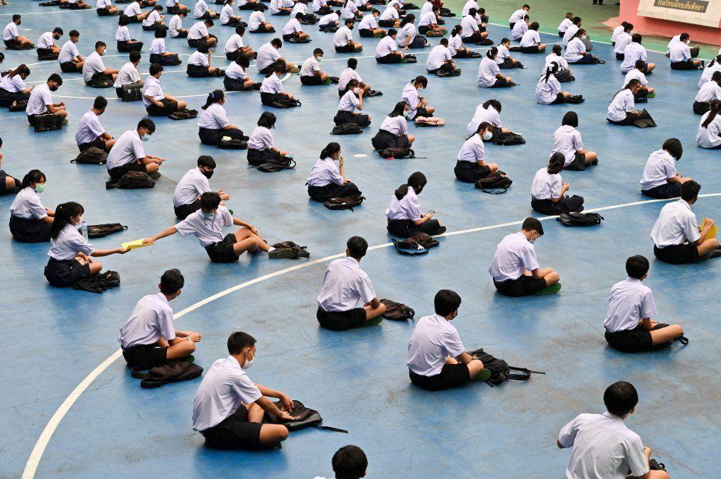 Estudiantes asistena la ceremonia de izamiento de la bandera en una escuela secundariaen Bangkok. Los alumnos en Tailandia regresaron a la escuela el 1 dejulio