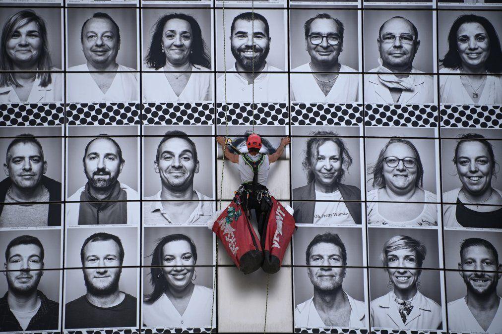 {altText(Un trabajador pega retratos de trabajadores de la salud en la fachada de la Opera Bastille, por iniciativa del colectivo #ProtegeTonSoignant para rendir homenaje a los cuidadores en la primera línea durante la epidemia de Covid-19, en París.,Las imágenes de la semana del 4 al 10 de julio 2020)}