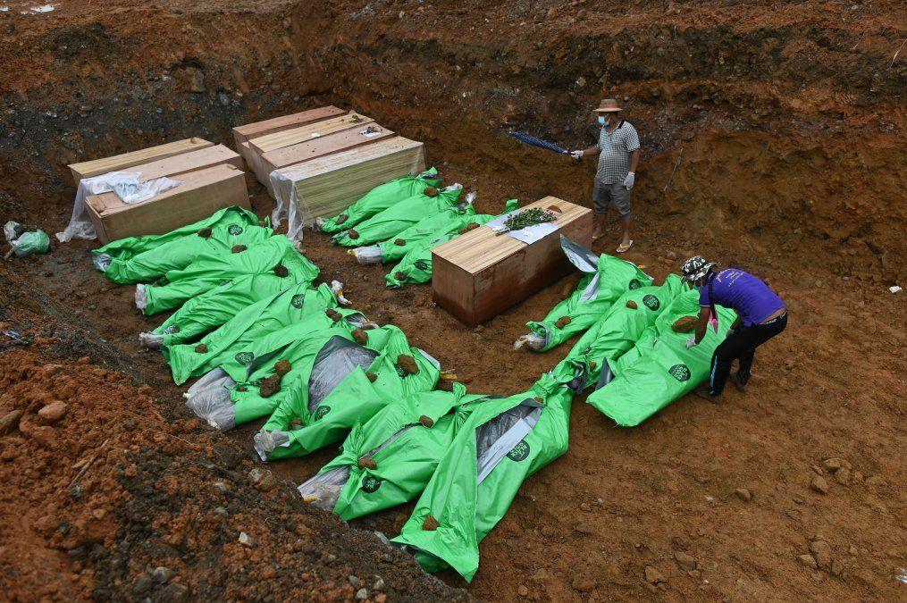 Los cuerpos de los mineros en ataúdes de madera y envueltos en bolsas se colocan en una fosa común antes de ser enterrados