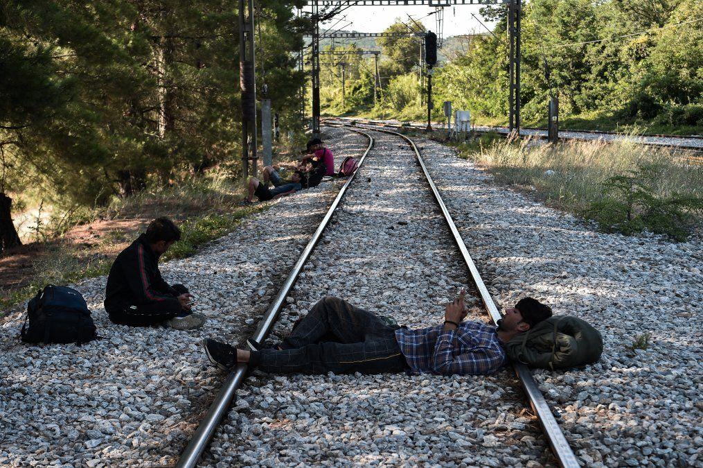 Migrantes descansan sobre la vía del tren cerca de la estación de Idomeni