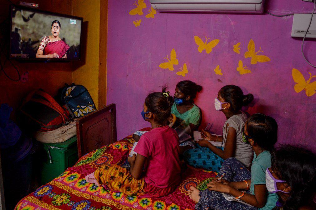 Niños miran una clase educativa por televisión que los habilita a continuar con las tareas curriculares en Chennai