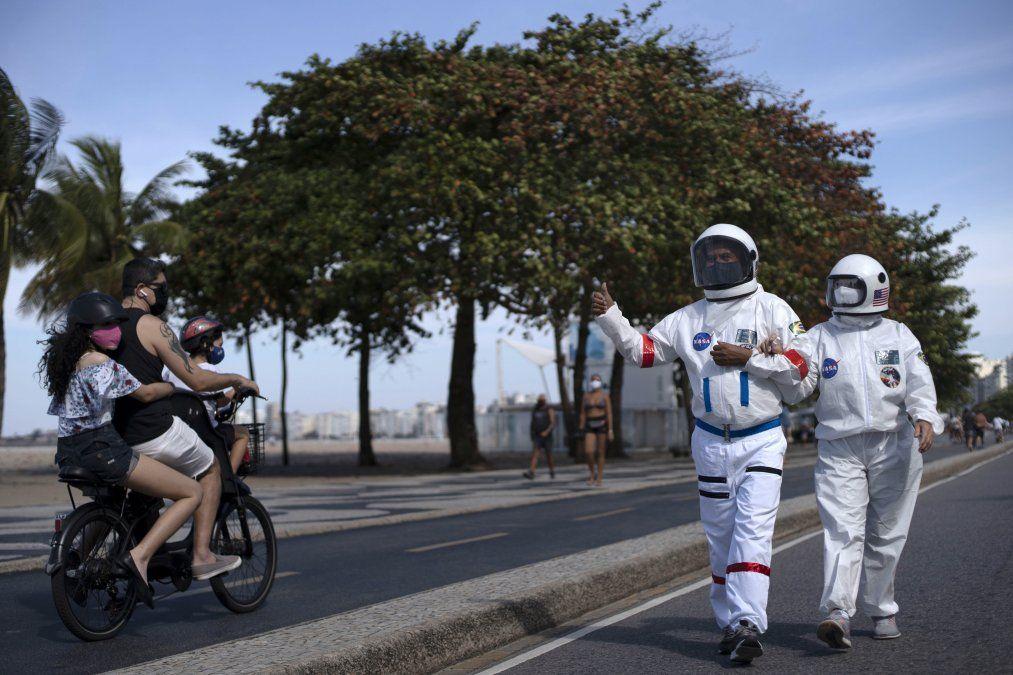 Una pareja de brasileños camina por Copacabana con trajes de astronauta para evitar contagiarse de coronavirus