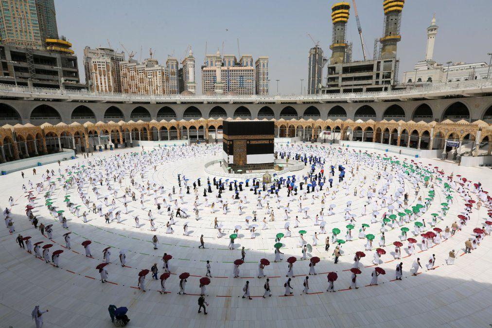 Peregrinos sostienen sombrillas de colores mientras circulan alrededor de la Kaabaen La Meca