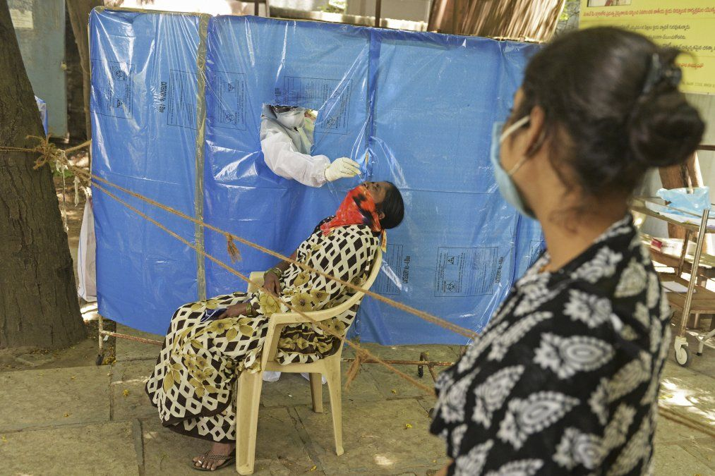 Un trabajador de la salud con traje de equipo de protección toma una muestra para el test de coronavirus en Hyderabad