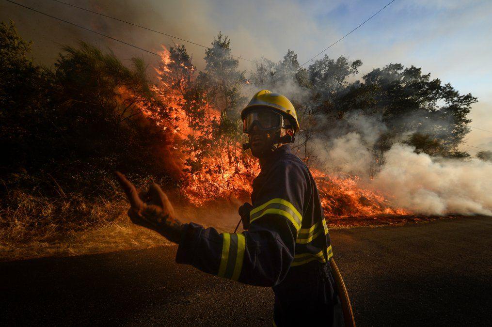 Un bombero intenta extinguir un incendio forestal en el pueblo de San Cristóbal