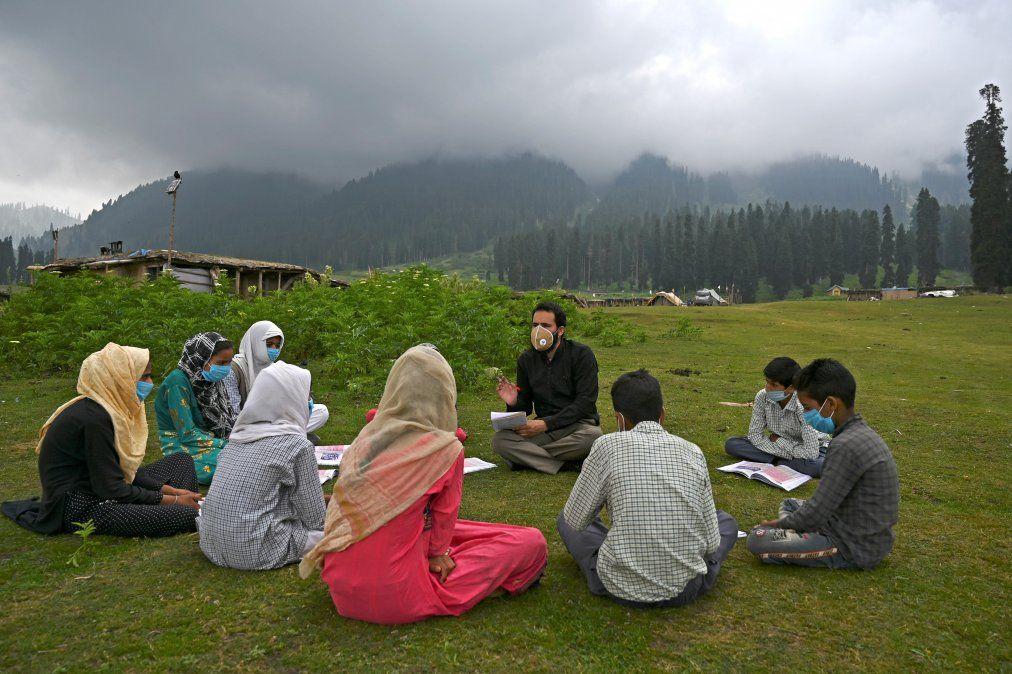 Los estudiantes asisten a una clase en su escuela al aire libre situada en la cima de una montaña en Doodhpathri.