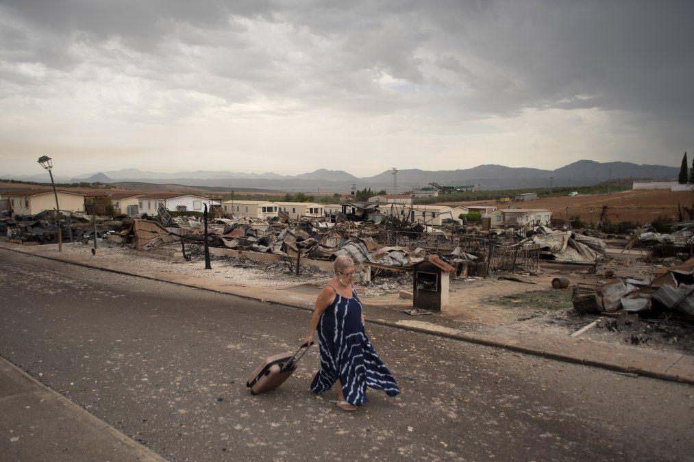 Una mujer camina por un parque de vacaciones quemado en Mollina