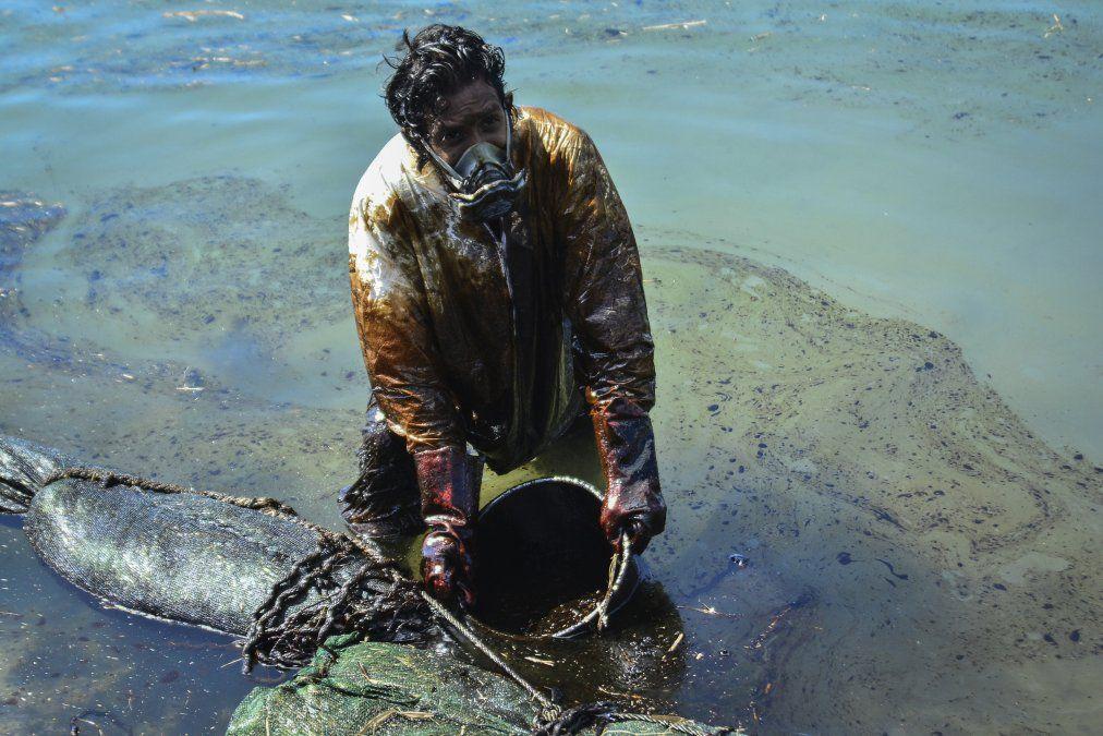 Un hombre extrae aceite derramado del buqye MV Wakashio que encalló cerca de Blue Bay frente a la costa sureste de Mauricio