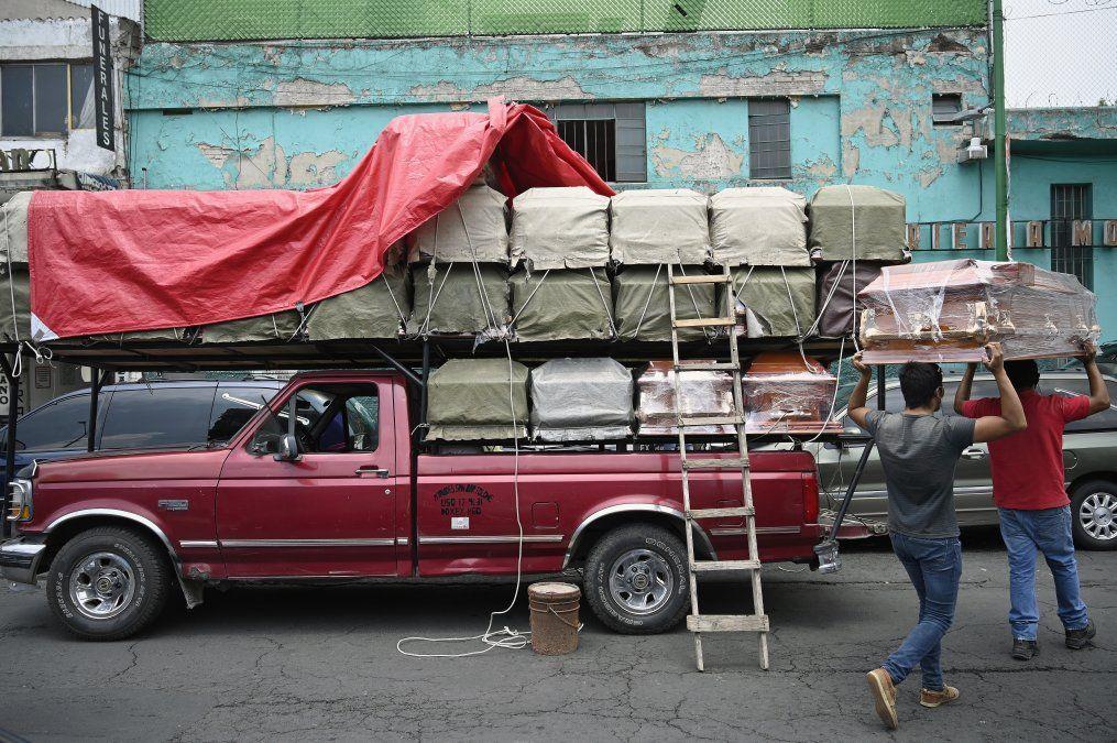 Trabajadores descargan ataúdes de un camión frente a una funeraria ubicada frente al Hospital General en la Ciudad de México