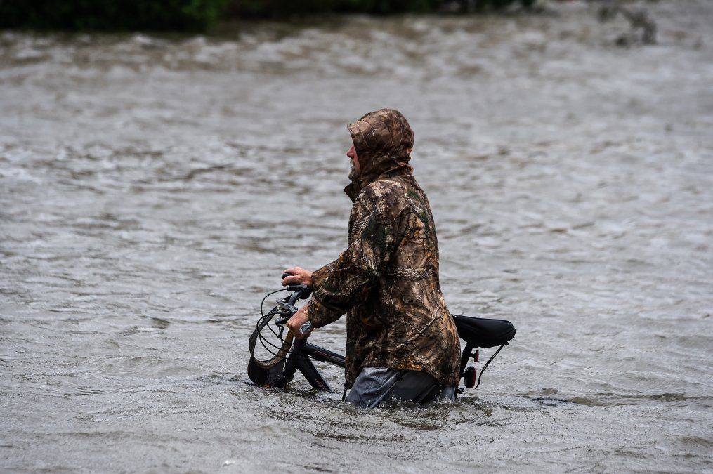 Un hombre camina junto a su bicicleta a lo largo de una calle inundada por el paso del Huracán Sally.