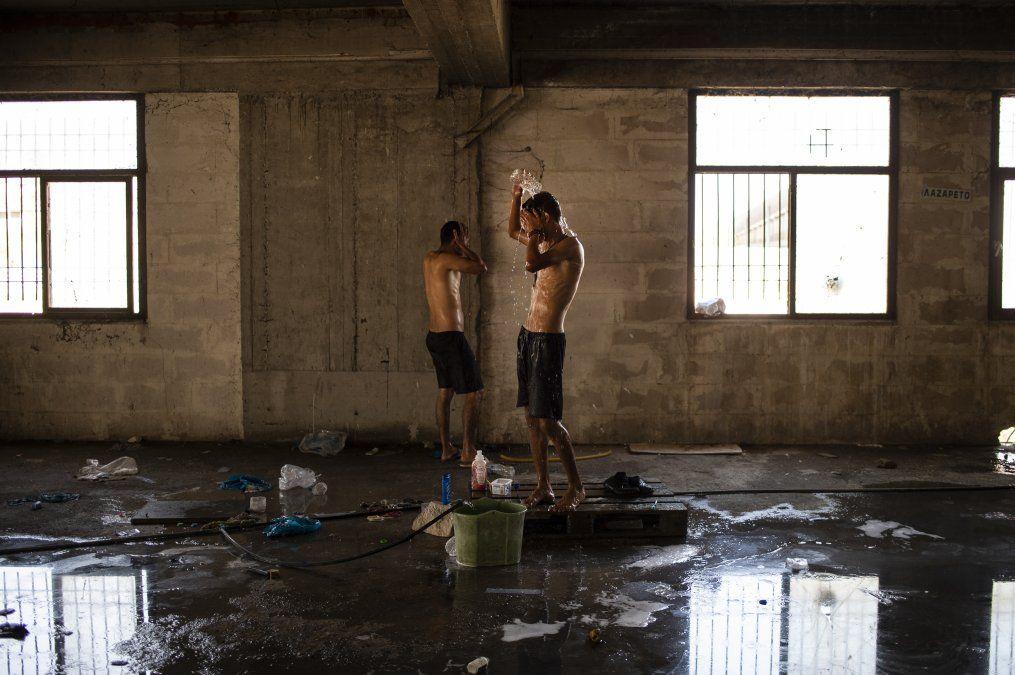 Dos migrantes se asean dentro de un edificio abandonado en el campamento de Kara Tape en la isla de Lesbos.