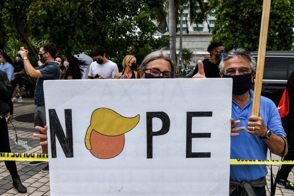Partidarios de Biden celebran en Miami con un cartel que hace referencia a Trump.