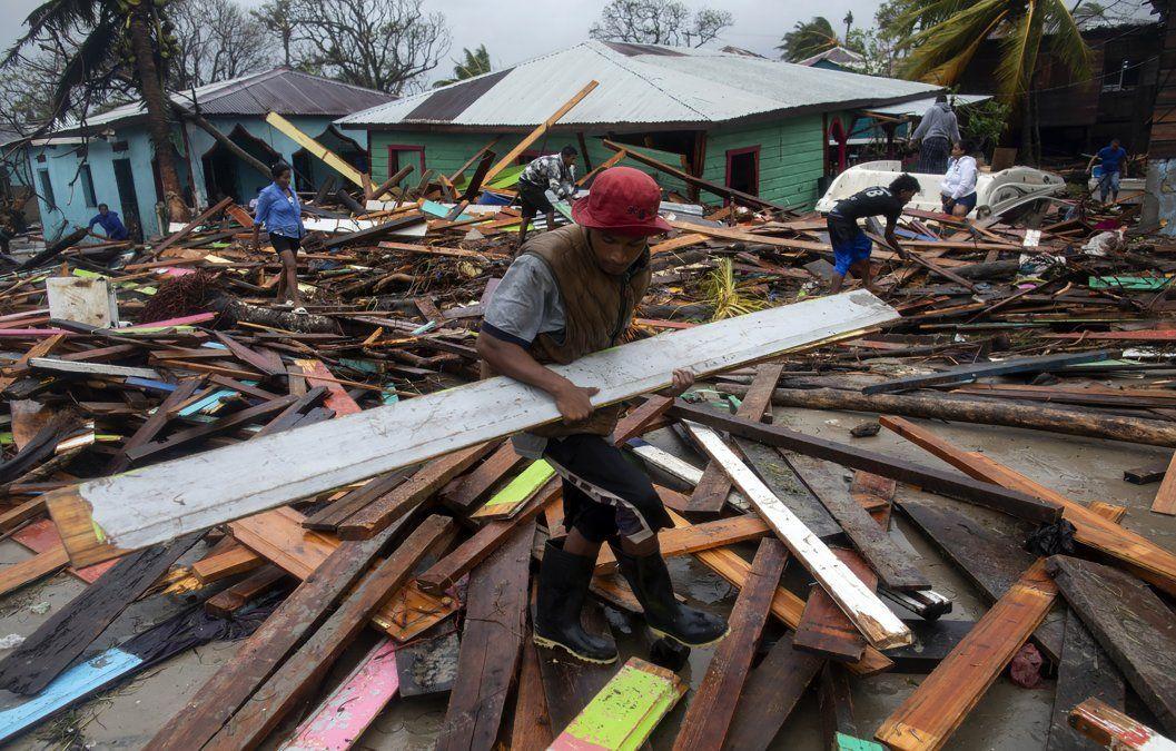 Un hombre carga un trozo de madera para arreglar su casa tras el paso del huracán Iota