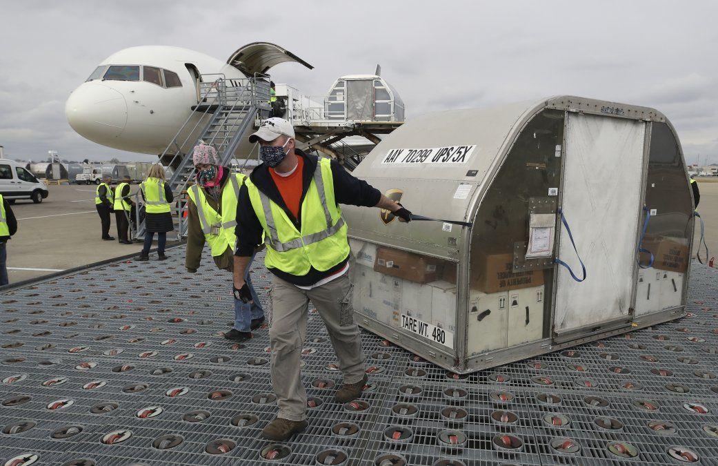 Empleados de la empresa de correos privada UPS transportan contenedores de la vacuna contra Covid-19 en el aeropuerto de Louisville