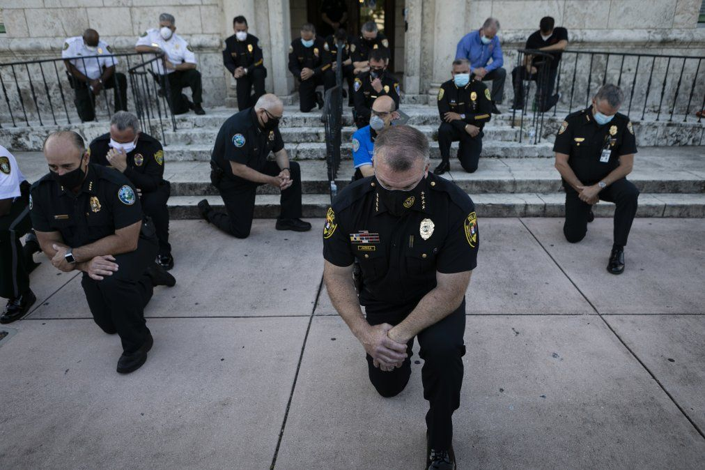 Oficiales de policía se arodillan en respuesta a la muerte de George Floyd a manos de un policía