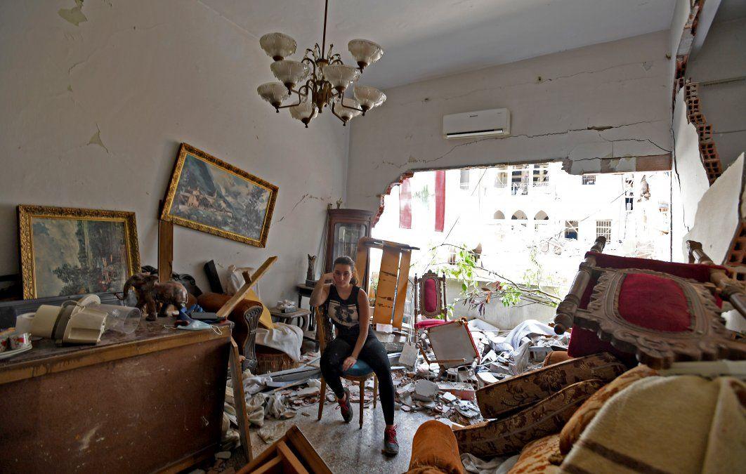 Una mujer sentada entre los escombros de su casa dañada dos días después que una explosión sacudiera la capital libanesa
