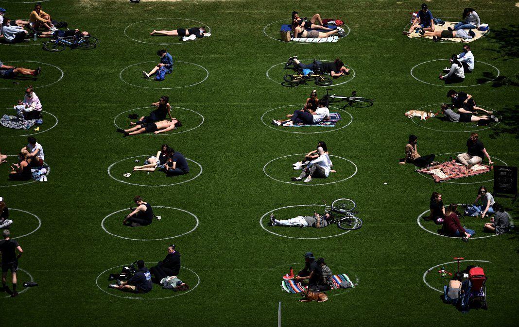 La gente es vista manteniendo distancia social dentro de círculos en el parque Domino de Brooklyn