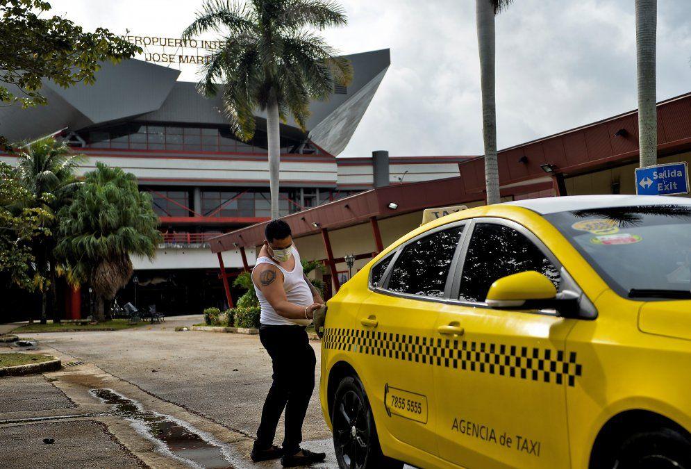 Taxista higieniza su coche en el Arropuerto Martí de La Habana.