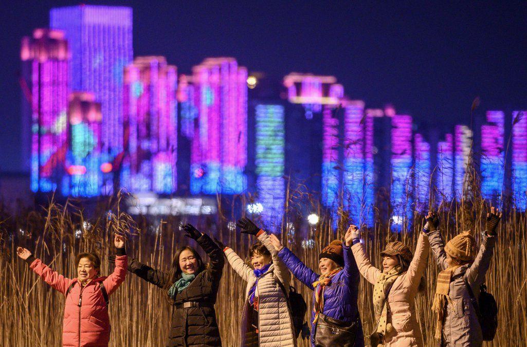 La gente posa para fotografías a orillas del río Yangtze en la víspera de Año Nuevo en Wuhan