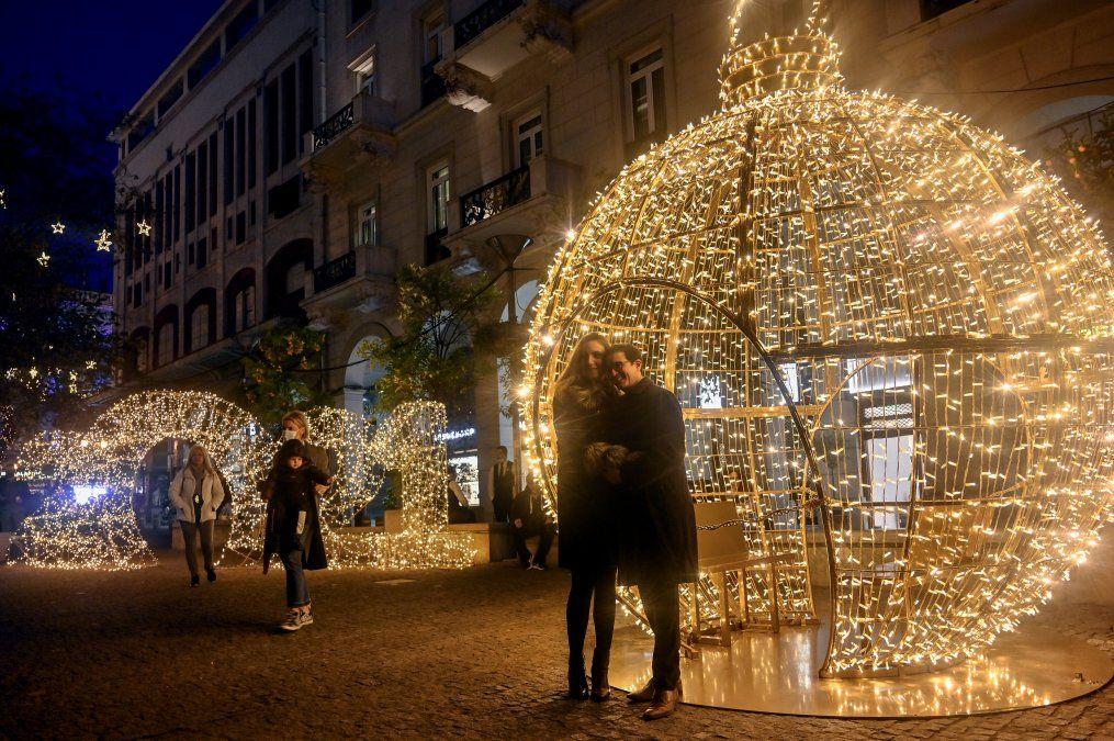 Personas posando frente a un letrero iluminado de 2021 en el centro de Atenas