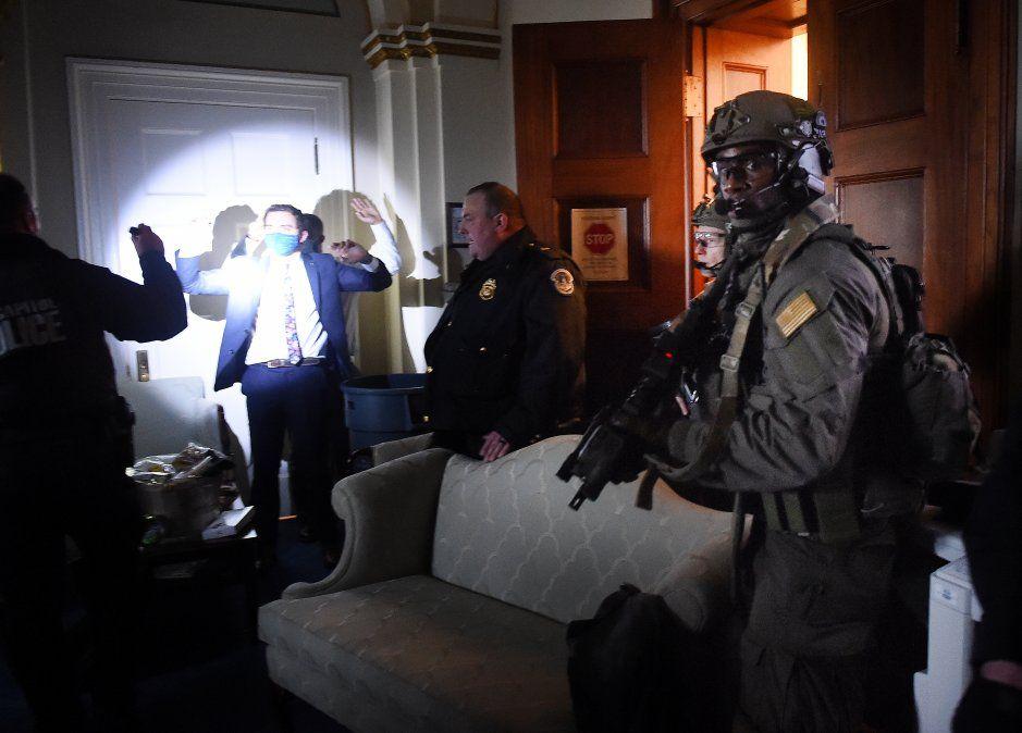 Personal del Congreso levanta las manos mientras los equipos Swat de la Policía del Capitolio revisan a todos en la sala mientras aseguran el piso.