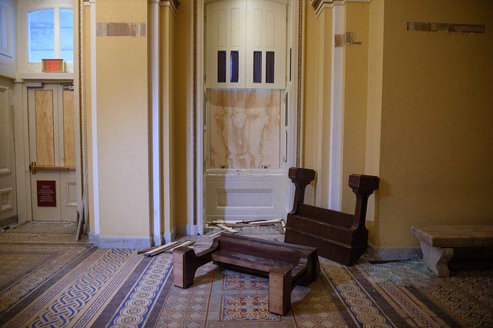 Muebles tirados y vidrios rotos en un pasillo del Capitolio de los Estados Unidos