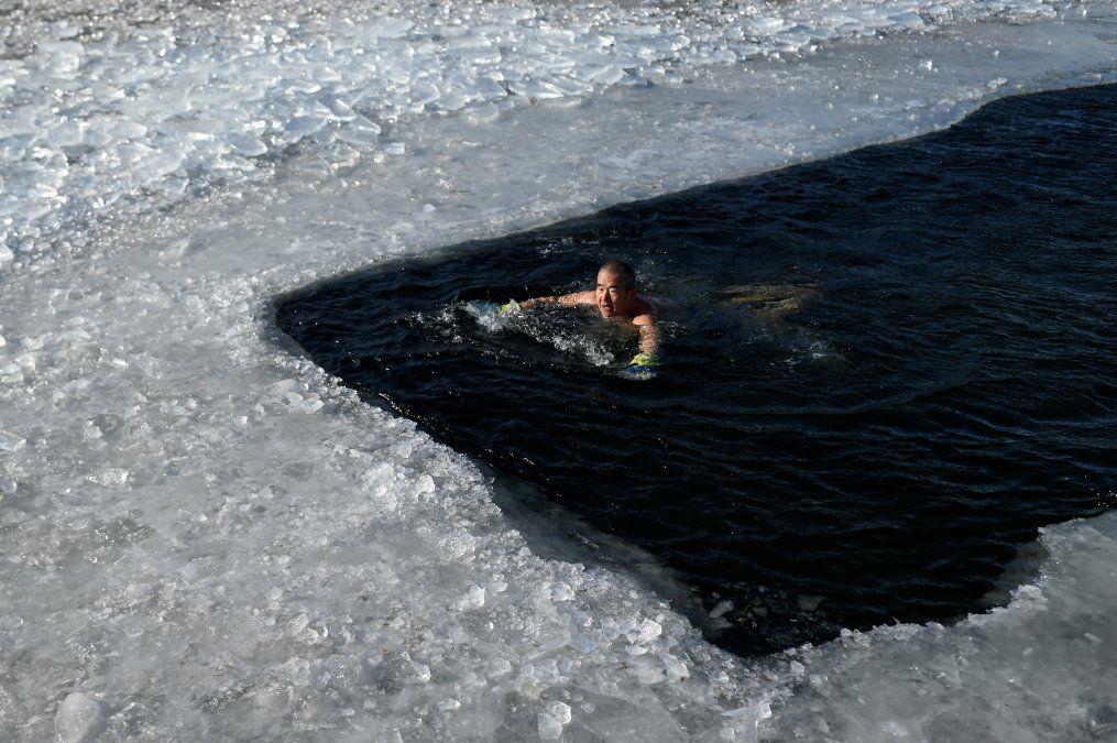 Un hombre nada en un lago congelado en un frío día de invierno en Beijing.