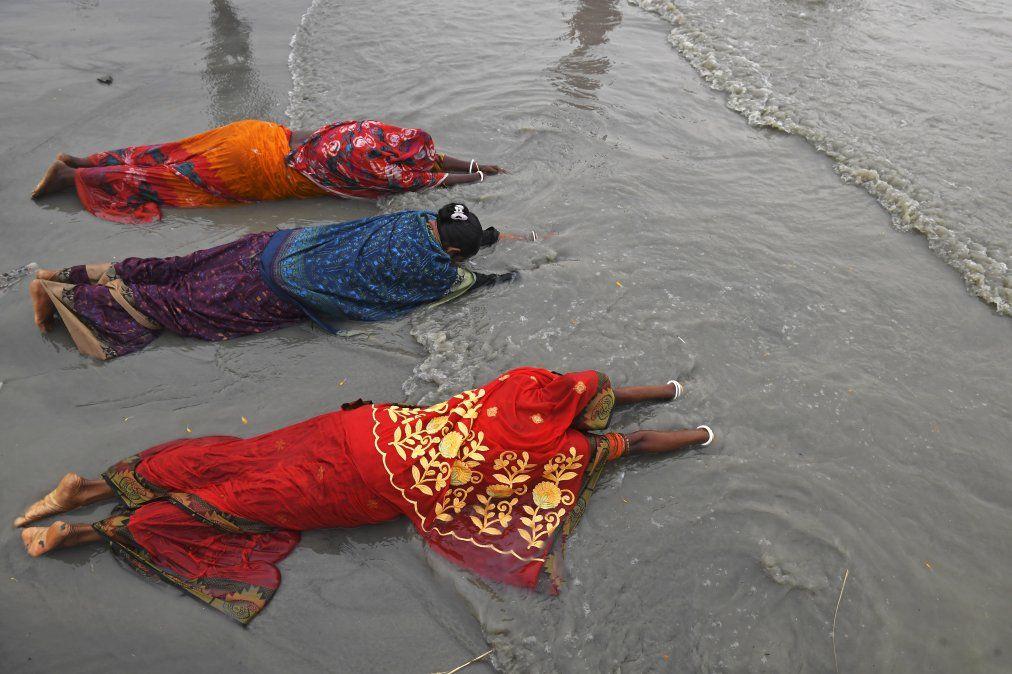 Los peregrinos hindúes ofrecen oraciones en la confluencia del Ganges y la Bahía de Bengala durante el Gangasagar Mela con motivo de Makar Sankranti