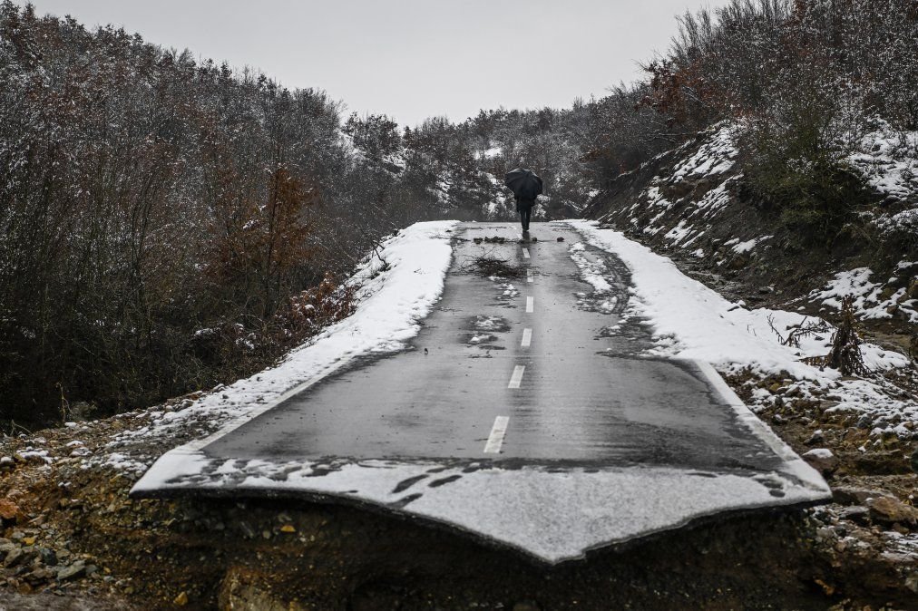 Un hombre pasa junto a una carretera colapsada debido a las fuertes inundaciones en la aldea de Sferke.