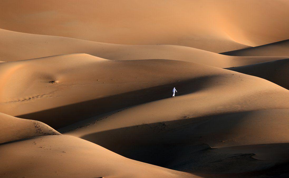 Un joven emiratí juega en las dunas de arena del desierto de Liwa
